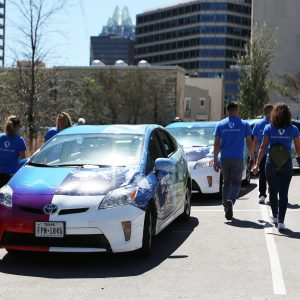 """Cool Effect hired a fleet of Priuses and a team of young """"brand ambassadors"""" to shuttle concertgoers people around Austin and engage them in discussions carbon offsetting. The shirts say, """"Earth, We're Here."""""""
